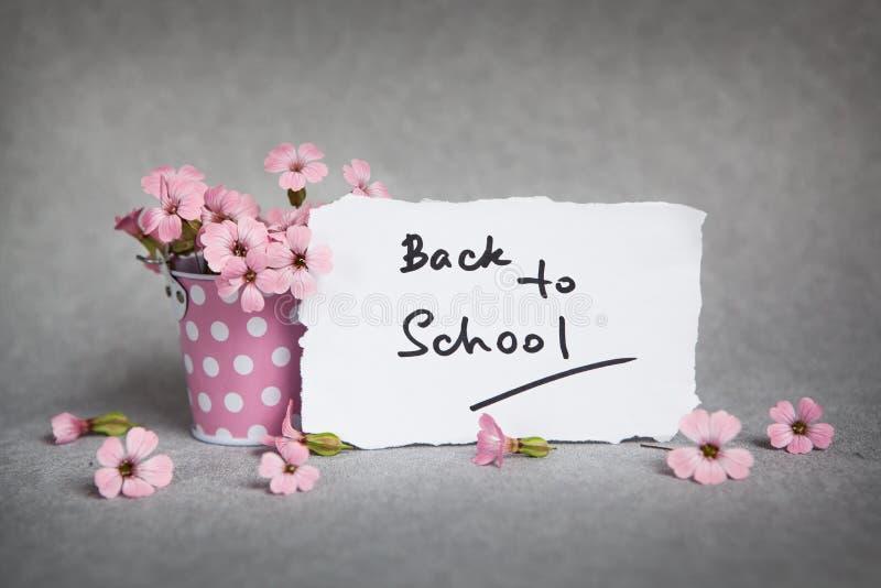 Dra tillbaka till skolan, ord med rosa blommor fotografering för bildbyråer