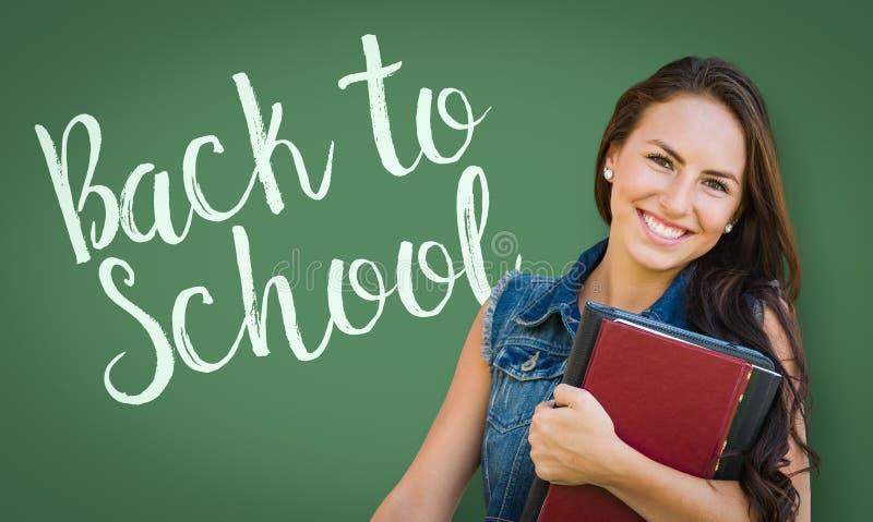 Dra tillbaka till skolan som är skriftlig på kritabräde bak det tonåriga blandade loppet royaltyfri foto