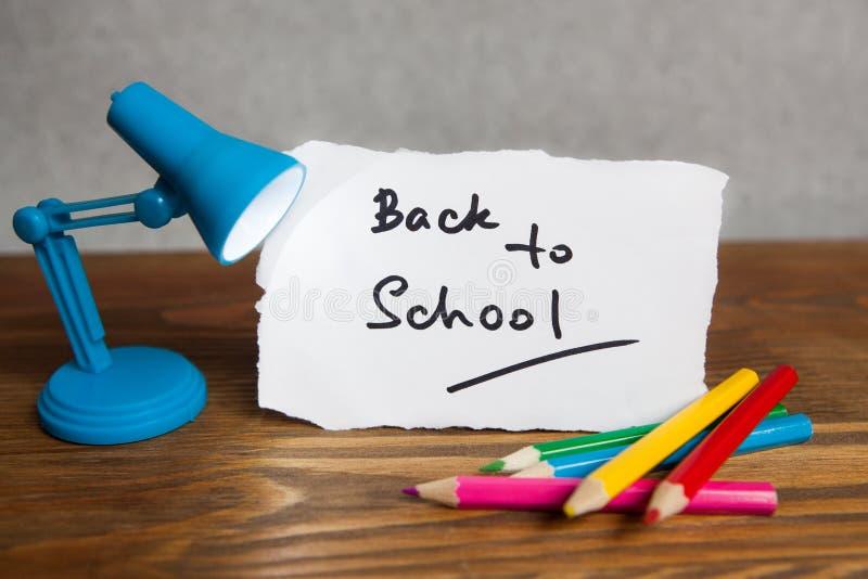 Dra tillbaka till skolaord med den små lampan och blyertspennor arkivfoton