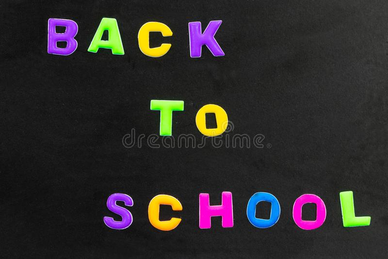 Dra tillbaka till skolatext som är skriftlig med färgrika bokstäver på svart tavla arkivbild