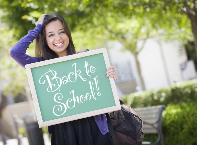 Dra tillbaka till studenten Holding Chalkboard för det blandade loppet för skolan den kvinnliga royaltyfri foto