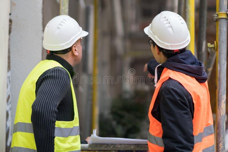 Dra tillbaka vända arbetare med skyddande arbetskläder som talar på konstruktionsplats royaltyfria bilder