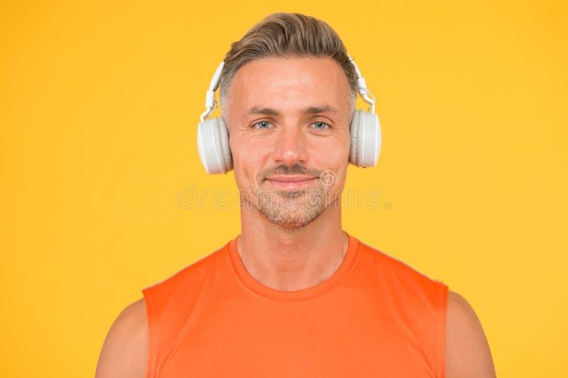 Draadloos is modern Schoon geluid Moderne technologie De mens luistert naar muziek draadloze gadget gele achtergrond Hipster stock afbeelding