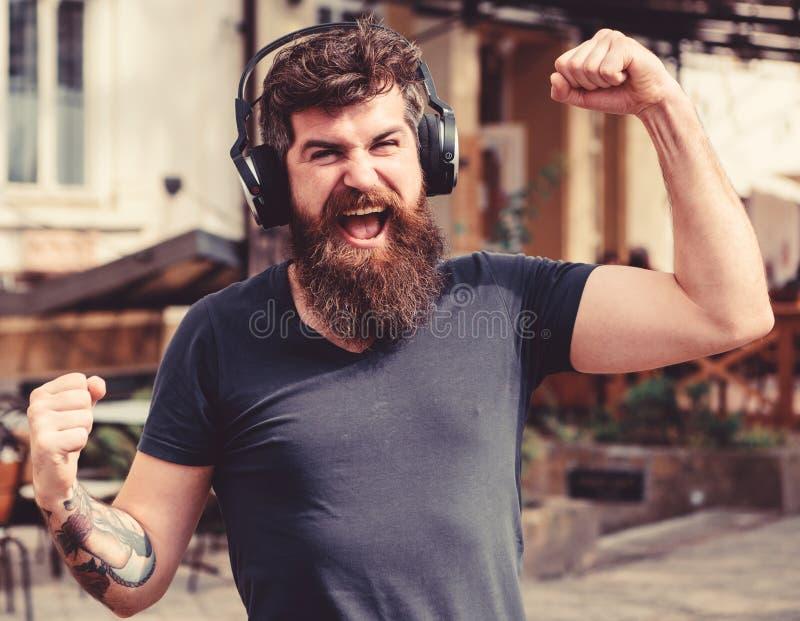 Draadloos technologieënconcept Hipster met hoofdtelefoons op gelukkige gezicht het luisteren muziek terwijl het lopen Mens met la royalty-vrije stock afbeelding