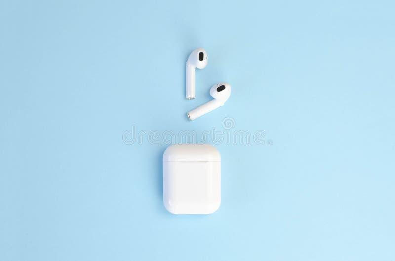 Draadloze witte hoofdtelefoons met een geval op een blauwe achtergrond royalty-vrije stock foto