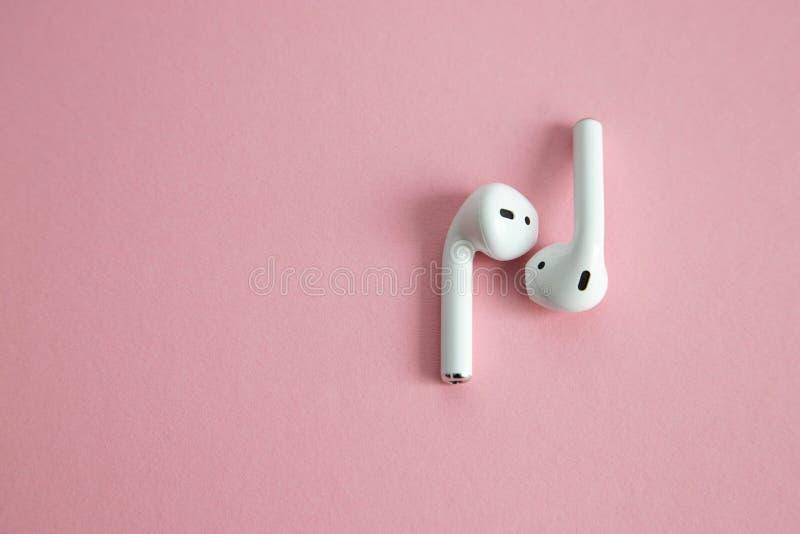 Draadloze witte hoofdtelefoons zonder koord, die naast elkaar op een roze achtergrond liggen Plaats voor tekst stock fotografie