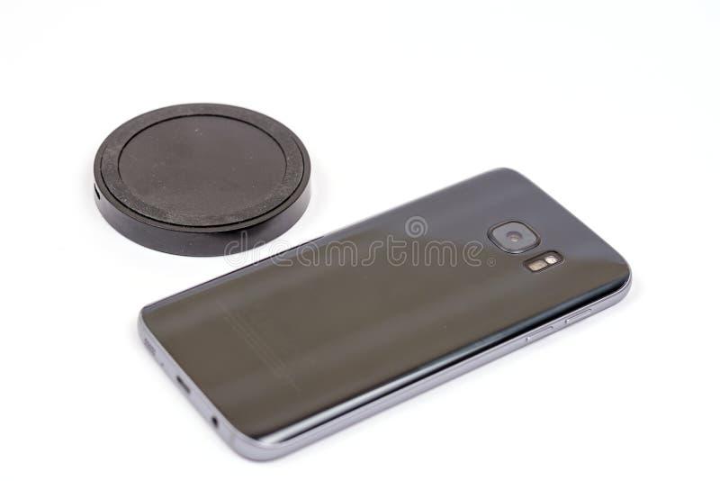 Draadloze zwarte mobiele lader met mobiele die telefoon over wh wordt geïsoleerd royalty-vrije stock fotografie