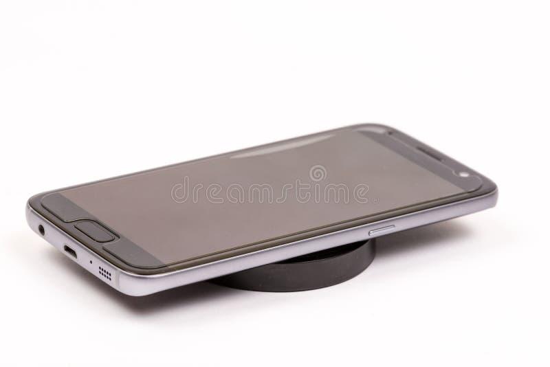Draadloze zwarte mobiele lader met mobiele die telefoon over witte achtergrond wordt geïsoleerd royalty-vrije stock afbeeldingen