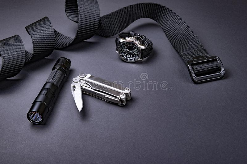 Draag EDC elke dag punten voor mensen in zwarte kleur - tactische riem, flitslicht, horloge en verzilver multihulpmiddel royalty-vrije stock afbeelding