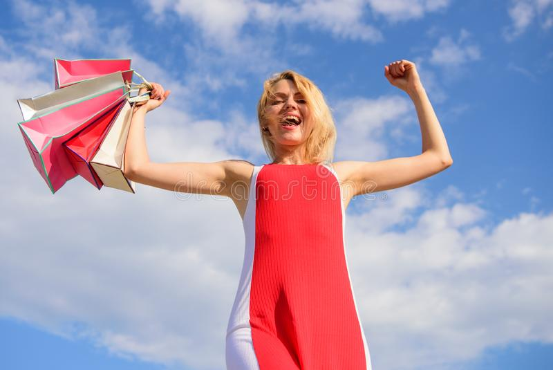 Draagt de vrouwen rode kleding bos het winkelen achtergrond van de zakken de blauwe hemel Meisje tevreden met aankopen Vind vrij  royalty-vrije stock fotografie