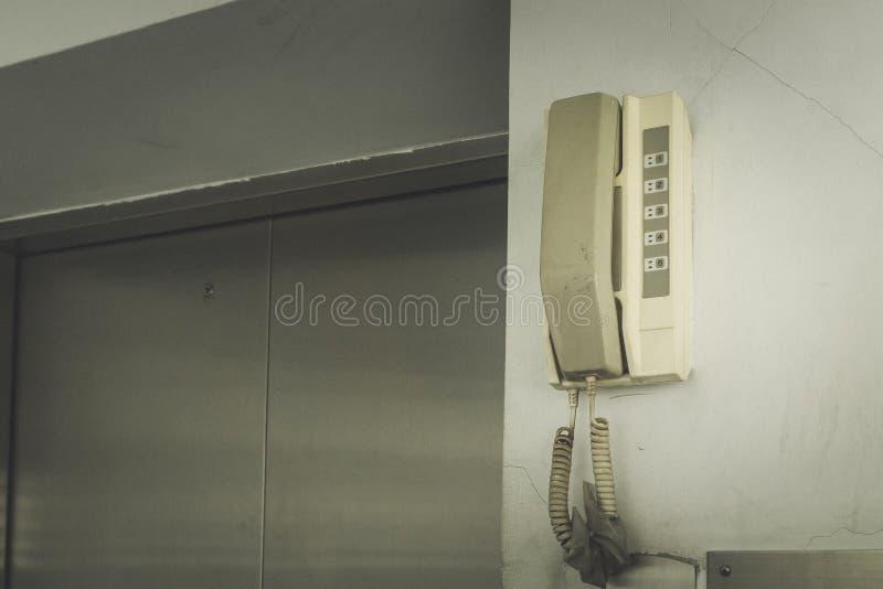 Draai de noodsituatie analoge telefoon die op de muur bij de lift hangen stock afbeelding