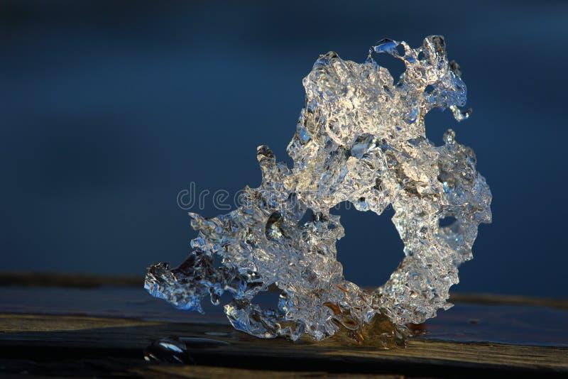 Draak-als brokken van ijs die in een meer in de lente tegen een strand worden gevangen stock fotografie