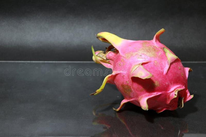 Draakfruit op de zwarte vloer De vorm is sferisch Beschikbaar in rood of purper stock fotografie
