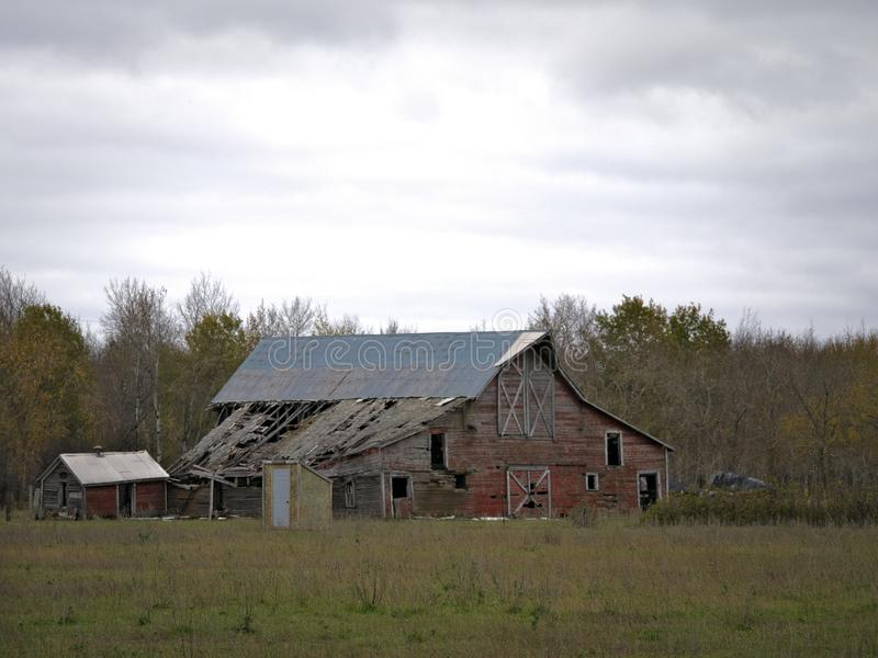 Drab Abandoned Dilapidated Farm Barn and Shed with clouds royalty free stock images