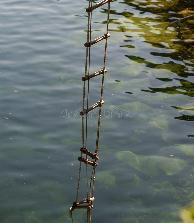 Drabina sukces nigdy tłoczy się przy wierzchołkiem Linowa drabina z drewnianymi krokami Arkana nad wody powierzchnią Ratunek lub obrazy stock