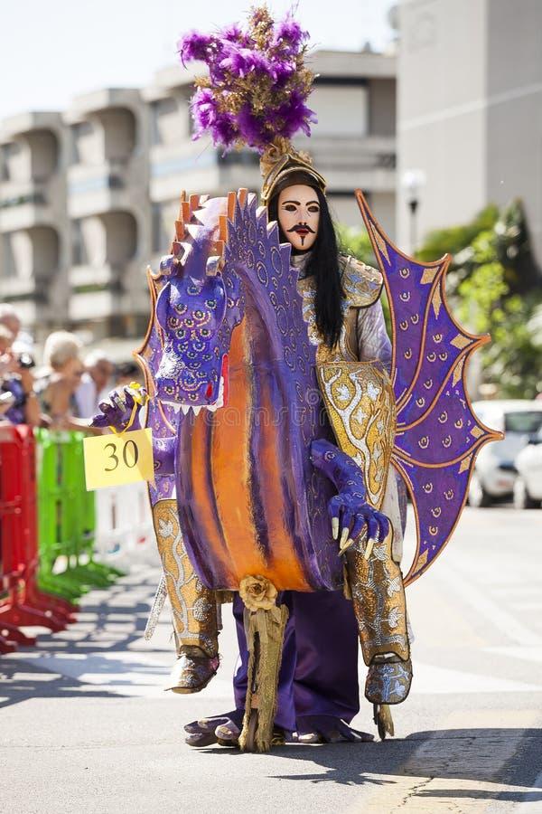 Drache mit einem Mann zu Pferd in der Karnevalsmaske stockbilder