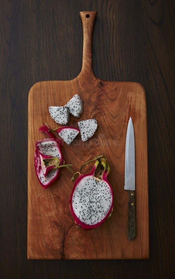 Drachefrucht schneiden und auf einem hölzernen Schneidebrett zugebereitet lizenzfreie stockfotografie