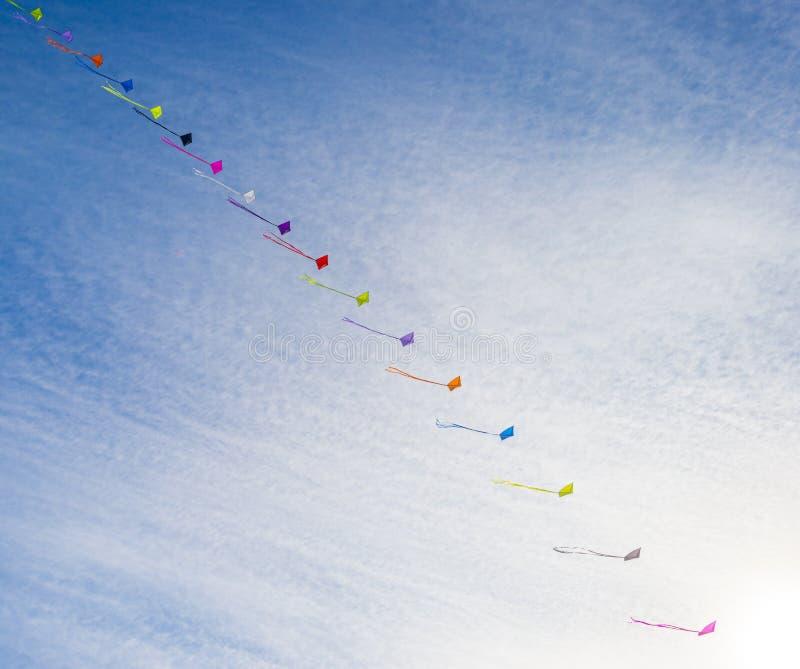 Drachen, die im Sonnenlicht in den Wind in einem blauen Himmel am Fall fliegen stockfoto
