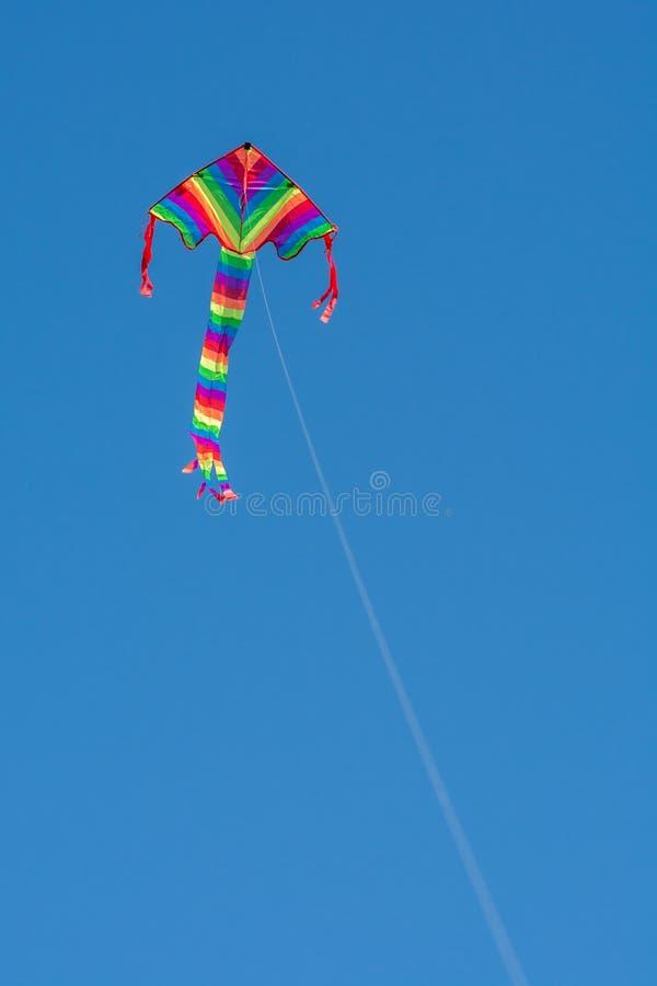 Drachen fliegt in den blauen Himmel lizenzfreie stockfotografie