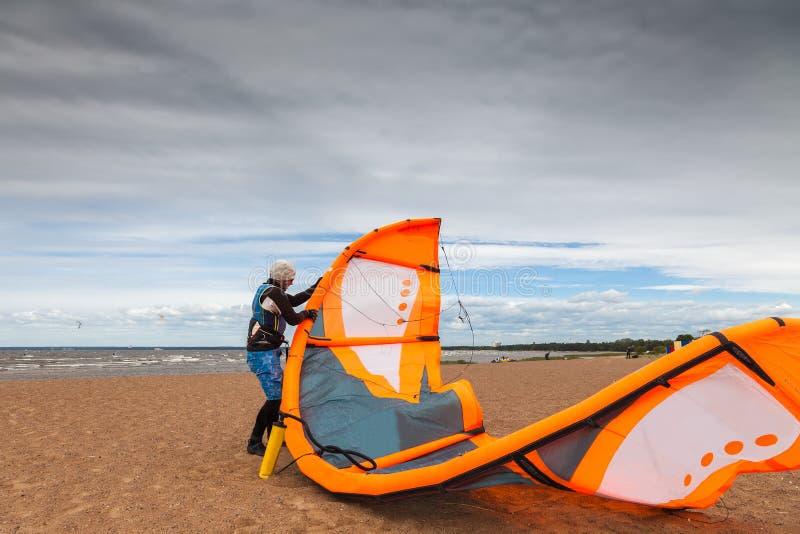 Drachensurfer bereitet seinen Drachen an einem windigen kalten Tag vor lizenzfreies stockfoto