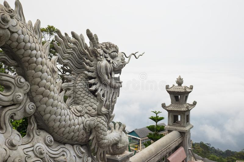 Drachestatue auf einen Hügel, über Wolken auf Hintergrund lizenzfreie stockfotos