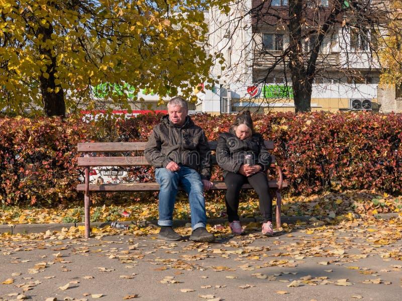Drack hemlösa par sitter på en bänk nära gångtunnelen arkivfoton