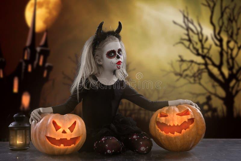Dracula-Kind kleines Mädchen mit Halloween-Make-up das Bild des Teufels mit Hörnern stockfotografie