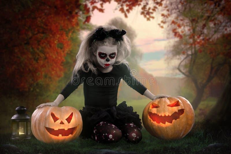 Dracula-Kind kleines Mädchen mit Halloween-Make-up das Bild des Teufels mit Hörnern lizenzfreies stockbild