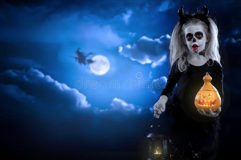 Dracula-Kind kleines Mädchen mit Halloween-Make-up das Bild des Teufels mit Hörnern stockbild