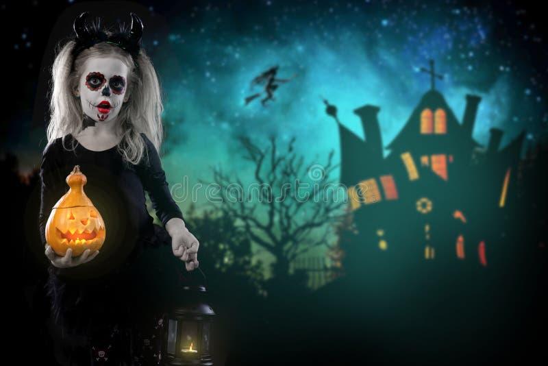 Dracula-Kind kleines Mädchen mit Halloween-Make-up das Bild des Teufels mit Hörnern stockfotos