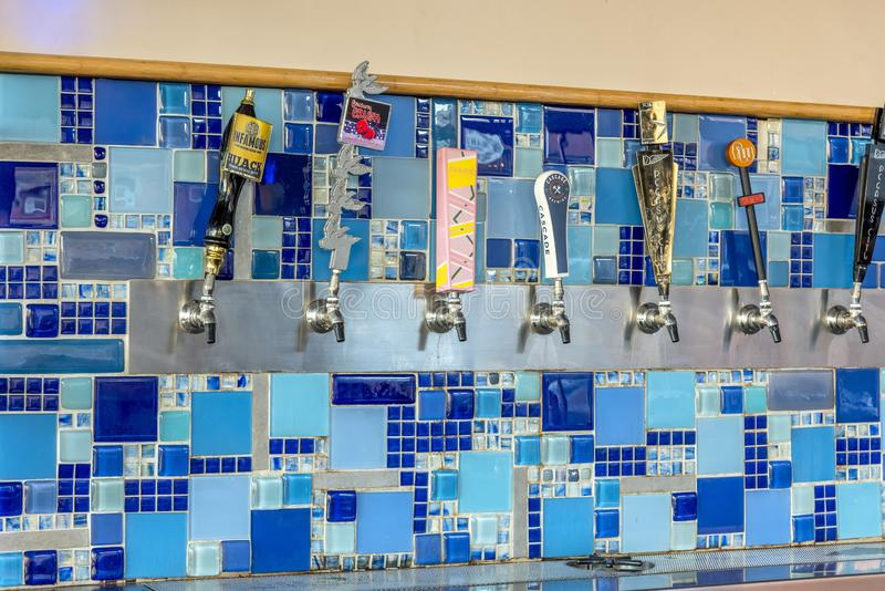 Draft beer machines on a blue wall captured in McKinney, Texas, United States. MCKINNEY, UNITED STATES - Dec 28, 2018: The draft beer machines on a blue wall stock image