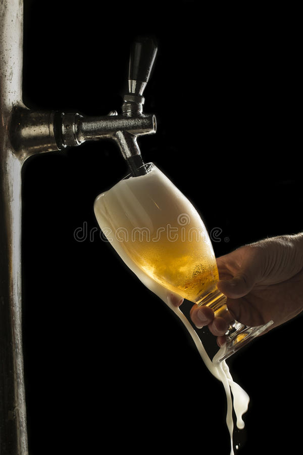 Draft beer overflows from the glass stock photo