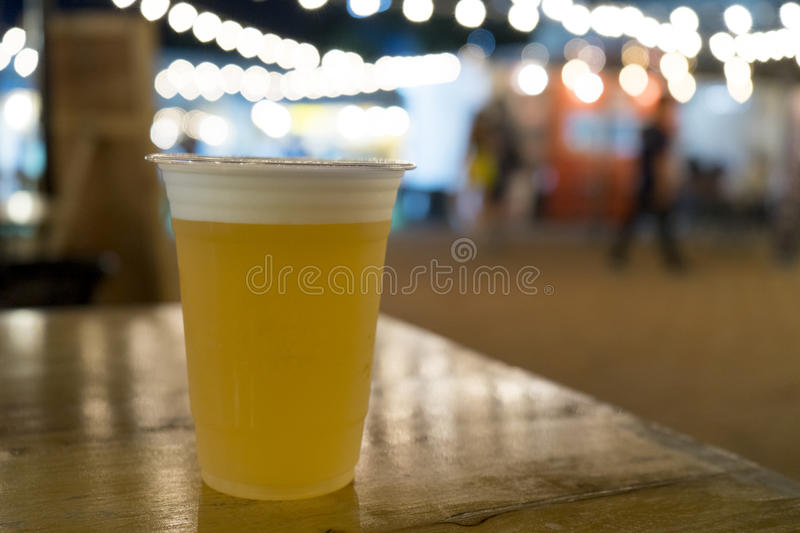 Draft beer in plastic cup on wooden table at festival with bokeh light.  royalty free stock photo