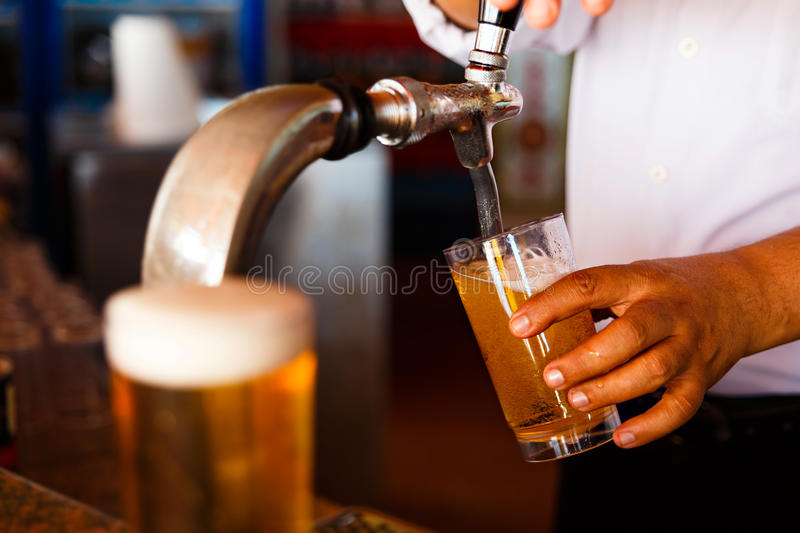 Draft beer. Pour in a glass from the crane stock photo