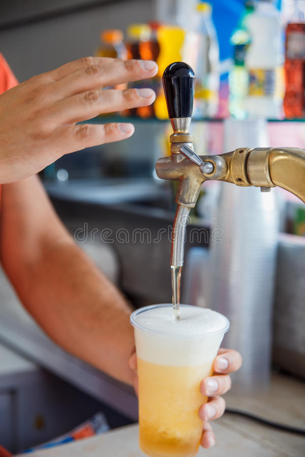 Draft beer pour. In a plastic cup from the crane stock photography