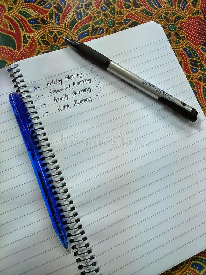 Draft on a notebook with blue and black ballpen. Of family planning financial planning work planning holiday planning stock photos