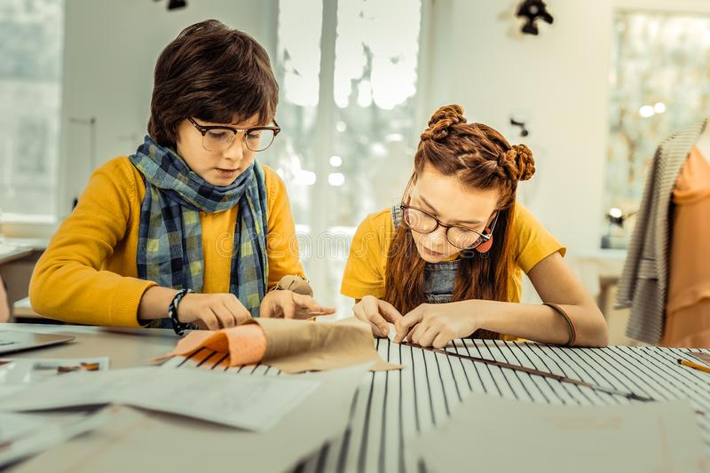 Creative future designers drafting patterns for clothes stock images