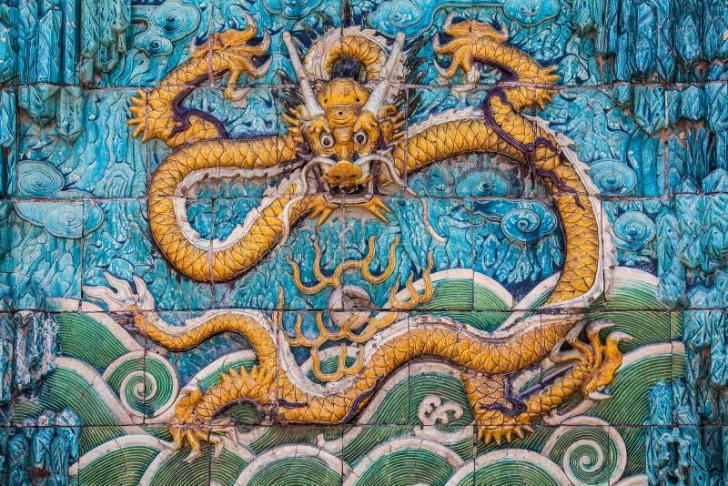 Dragão amarelo com forepaws levantados na parede fotos de stock