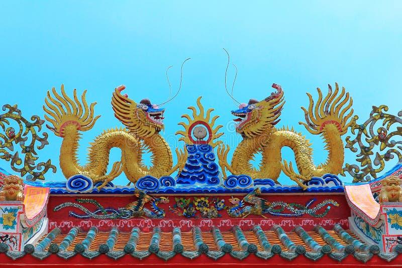 Dragón chino de oro gemelo en el tejado superior para la decoración exterior en el cielo azul, templo del chino del lugar santo imagen de archivo libre de regalías