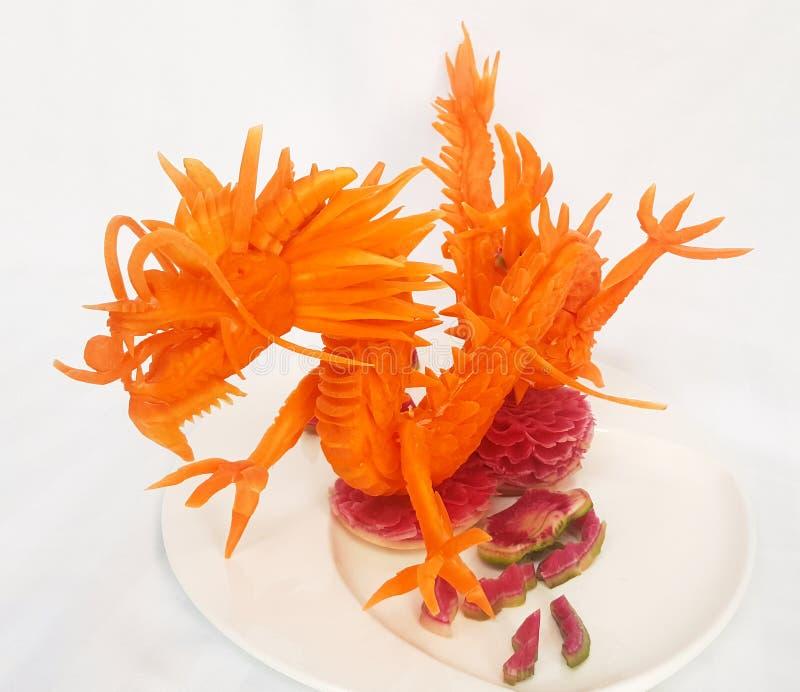 Dragón rojo tallado de una zanahoria en un fondo blanco - comida que talla cerca encima de imagen imágenes de archivo libres de regalías