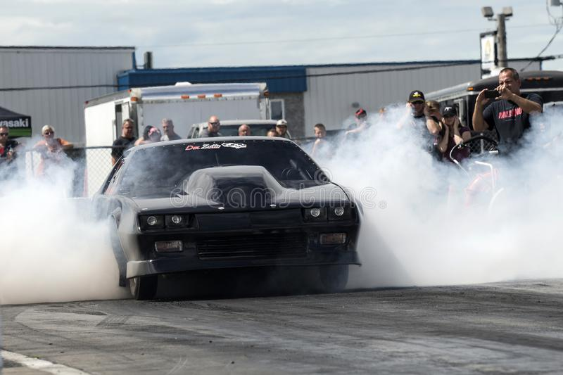 Drag car smoke show. Front view of black chevrolet camaro drag car on the track making a smoke show at the starting line during the john scotti all out august 17 stock image