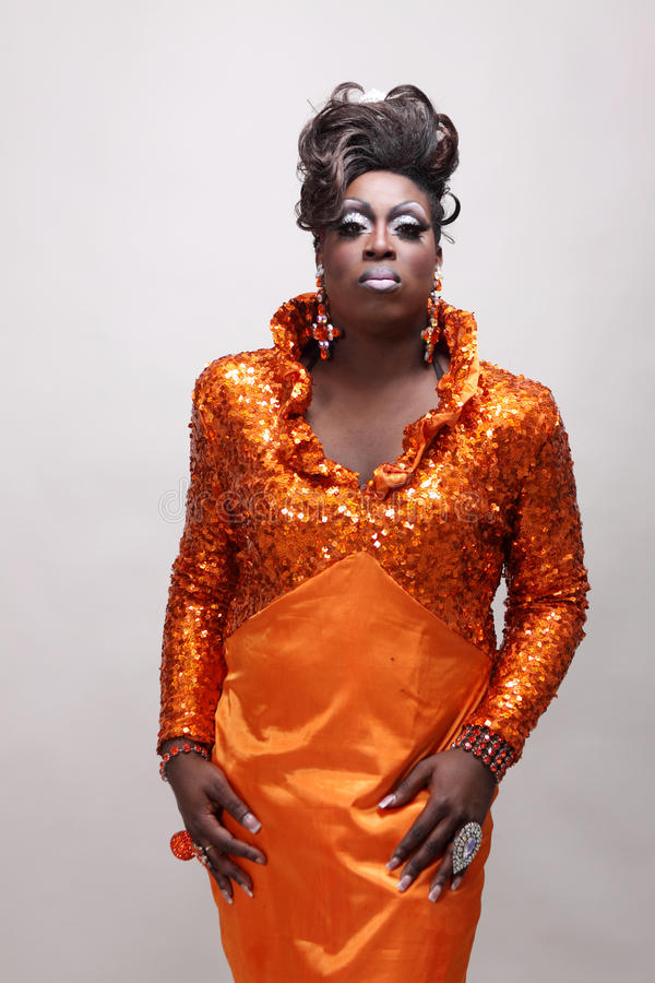 Drag queen. Wearing an orange gown with sequins stock photos