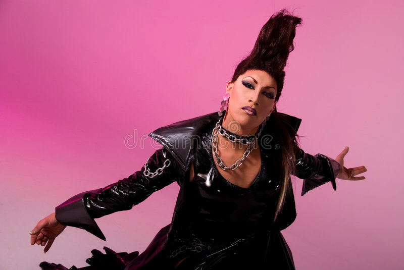 Drag queen. Drag queen wearing a long latex cape performing her routine, a pink gel over the background light makes the background pink royalty free stock images
