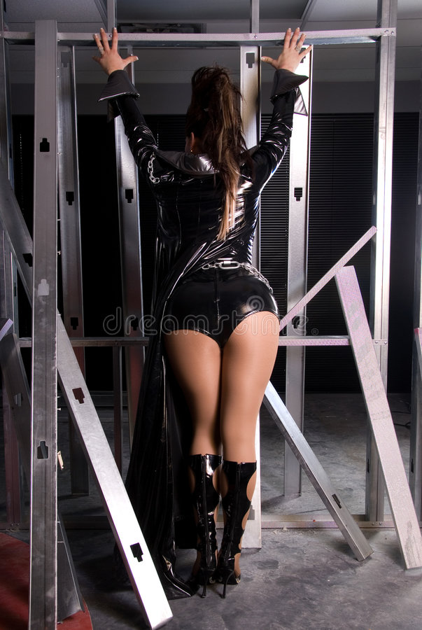 Drag queen. Back view of a drag queen wearing latex outfit posing in a construction area royalty free stock photos
