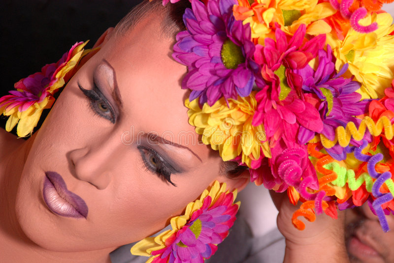 Drag queen. Close up of a Drag queen wearing a colorful flower head piece stock photo