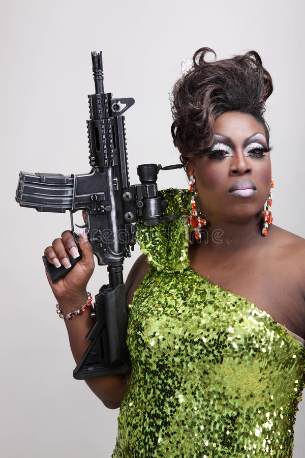 Drag queen with gun. Drag queen wearing a green gown holding an assault rifle royalty free stock photos