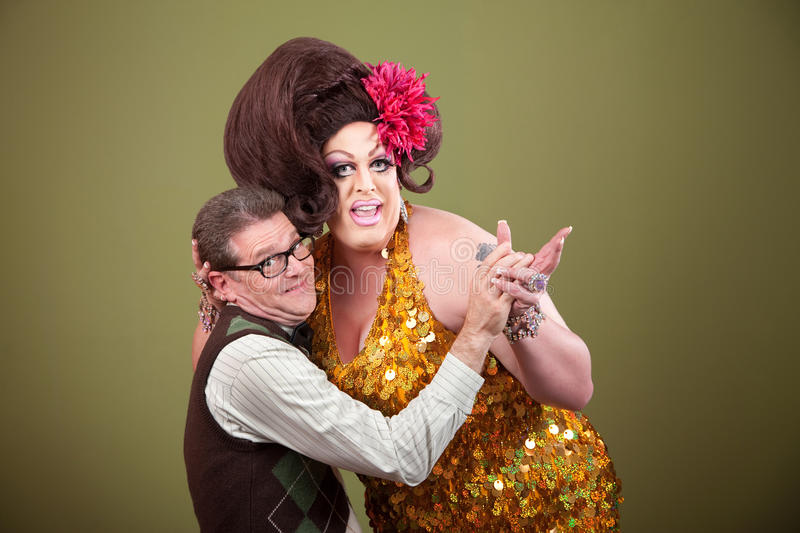 Drag Queen Holding Nerd. Drag queen and Caucasian nerd on green background hold hands royalty free stock image
