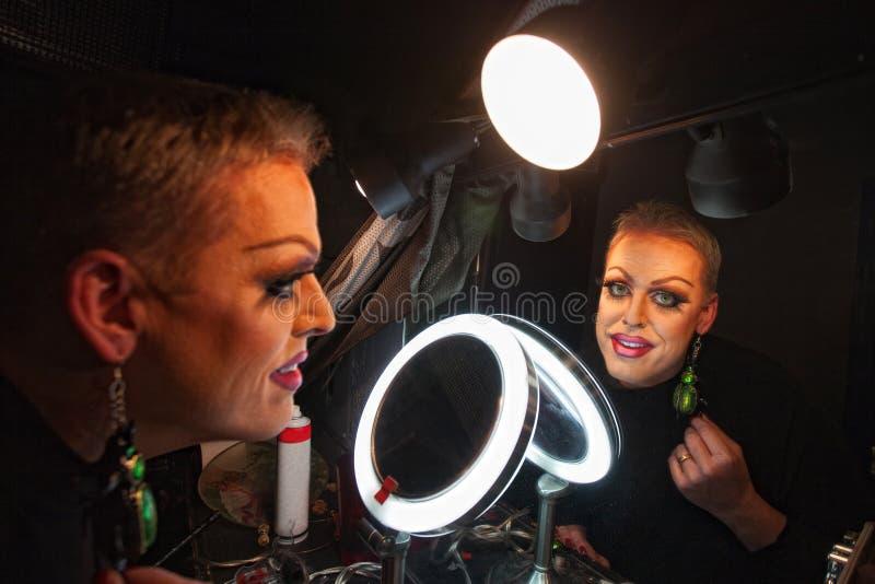Drag Queen in Makeup Room. Caucasian drag queen at mirror in dressing room royalty free stock photos
