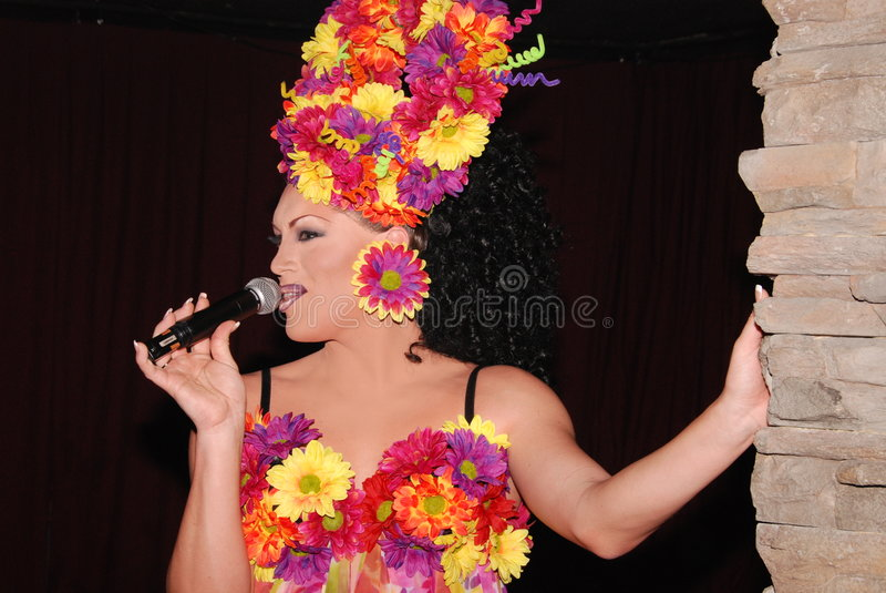 Drag queen singing. Gorgeous Drag queen, wearing a flamboyant flower dress and head piece, singing into a microphone stock images