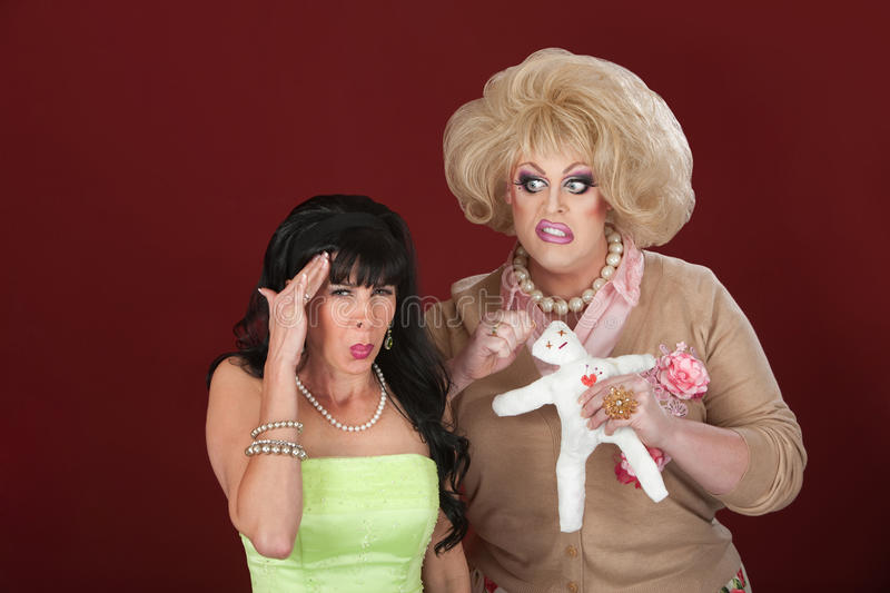 Drag Queen With Voodoo Doll. Large drag queen with voodoo doll casts a spell on woman stock photo